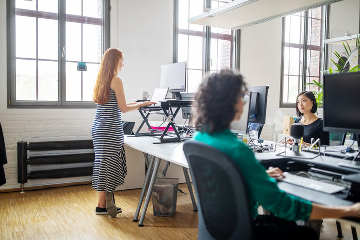Ergonomic keyboard tray arm, woman standing at sit/stand desk